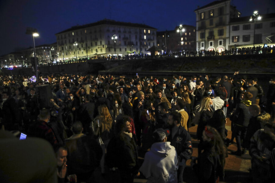 People gather at the Darsena dei Navigli, in Milan, Italy, Saturday, Feb. 27, 2021. Police vans blocked entrance to Milan's trendy Navigli neighborhood Saturday evening after the mayor announced increased patrols to prevent gatherings during a spring-like weekend. The Lombardy region where Milan is located is heading toward a partial lockdown on Monday, and Mayor Giuseppe Sala said in a video message that he was disturbed by scenes of people gathering in public places, often with their masks down. (AP Photo/Luca Bruno)