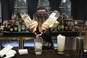 A bartender mixes a drink while wearing a mask and face shield at Slater's 50/50 Wednesday, July 1, 2020, in Santa Clarita, Calif. California Gov. Gavin Newsom has ordered a three-week closure of bars, indoor dining and indoor operations of several other types of businesses in various counties, including Los Angeles, as the state deals with increasing coronavirus cases and hospitalizations. (AP Photo/Marcio Jose Sanchez)