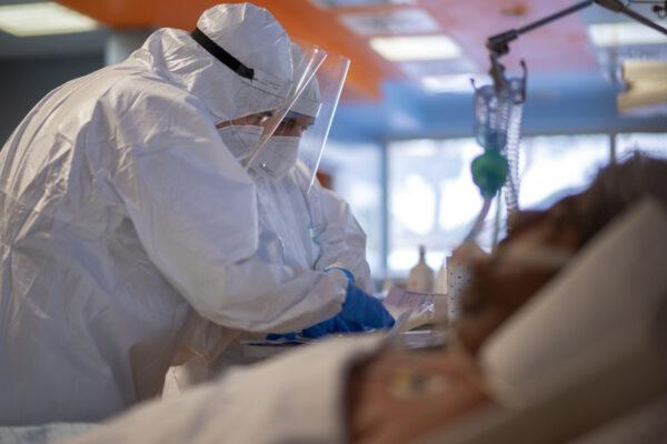 Head surgeon Sebastiano Petracca, right, and head nurse Mirco Perruzza, check the record for a patient with coronavirus in the ICU of the ICC Casalpalocco COVID-19 spoke hospital in Rome, Wednesday, Nov. 25, 2020. (AP Photo/Domenico Stinellis)