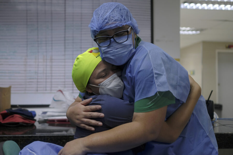 Health workers of the COVID-19 area embrace at the end of their shift at the Ana Francisca Perez de Leon II public Hospital in Caracas, Venezuela, Tuesday, March 23, 2021. (AP Photo/Matias Delacroix)