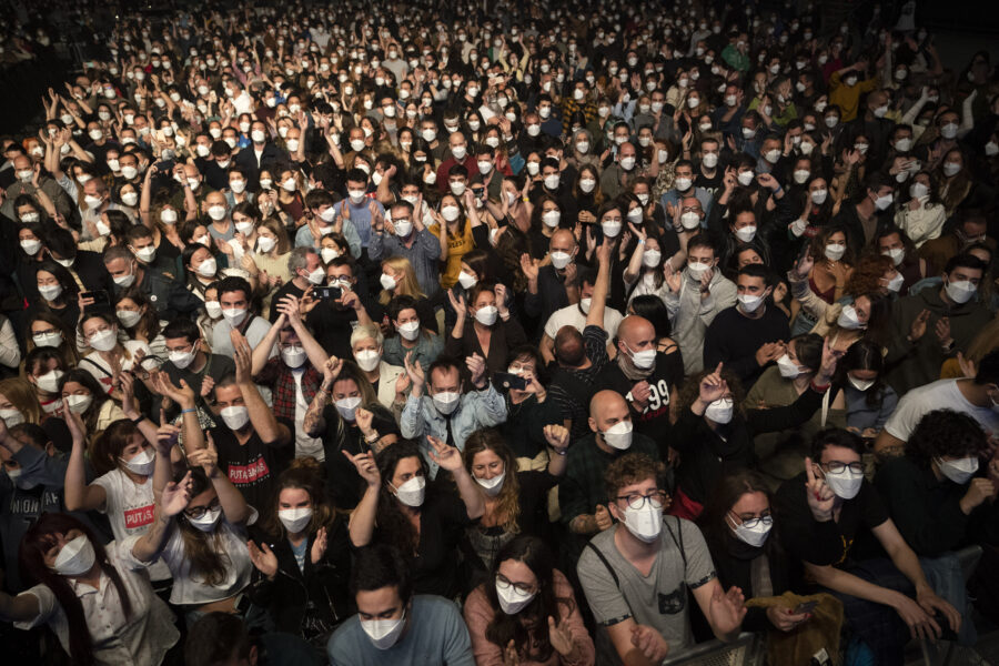 People react ahead of a music concert in Barcelona, Spain, Saturday, March 27, 2021. Five thousand music lovers are set to attend a rock concert in Barcelona on Saturday after passing a same-day COVID-19 screening to test its effectiveness in preventing outbreaks of the virus at large cultural events. The show by Spanish rock group Love of Lesbian has the special permission of Spanish health authorities. While the rest of the country is limited to gatherings of no more than four people in closed spaces, the concertgoers will be able to mix freely while wearing face masks. (AP Photo/Emilio Morenatti)