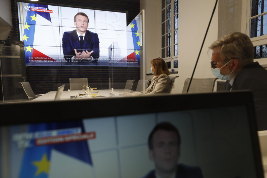 Local prefect Josiane Chevalier, second right, and her aide watch French President Emmanuel Macron addressing the nation, in the local government building in Strasbourg, eastern France, Wednesday, March 31, 2021. French President Macron announced 3-week nationwide school closure, domestic travel ban amid virus surge. (AP Photo/Jean-Francois Badias)
