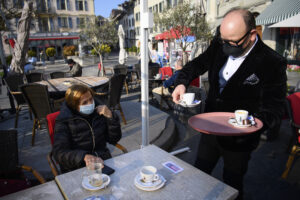 """A waiter wearing a face protection mask serves a coffee on the terrace of the """"Restaurant Le Leman"""" the opening day of the terrace, restaurants can only open their terraces but indoor rooms remain closed, during the coronavirus disease (COVID-19) outbreak in Nyon, Switzerland, Monday, April 19, 2021. (Laurent Gillieron/Keystone via AP)"""