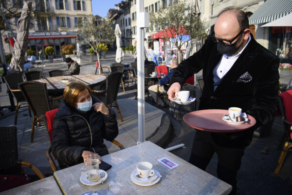 "A waiter wearing a face protection mask serves a coffee on the terrace of the ""Restaurant Le Leman"" the opening day of the terrace, restaurants can only open their terraces but indoor rooms remain closed, during the coronavirus disease (COVID-19) outbreak in Nyon, Switzerland, Monday, April 19, 2021. (Laurent Gillieron/Keystone via AP)"