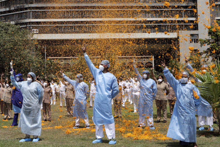 FILE – In this May 3, 2020, file photo, an Indian Air Force helicopter showers flower petals on the staff of INS Asvini hospital in Mumbai, India. The event was part the Armed Forces' efforts to thank the workers, including doctors, nurses and police personnel, who have been at the forefront of the country's battle against the COVID-19 pandemic. India's death toll from COVID-19 has surpassed 200,000 as a virus surge sweeps the country, rooted in so-called super-spreader events that were allowed to happen in the months following the autumn when  the country had seemingly brought the pandemic under control. (AP Photo/Rajanish Kakade, File)