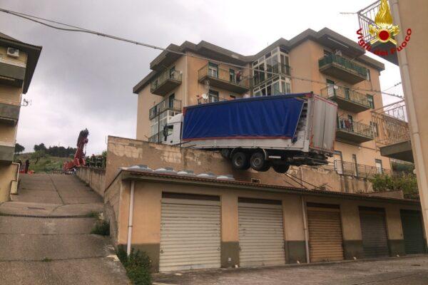 Camion 'sospeso' sul tetto rischia di cadere su una palazzina: evacuati i residenti