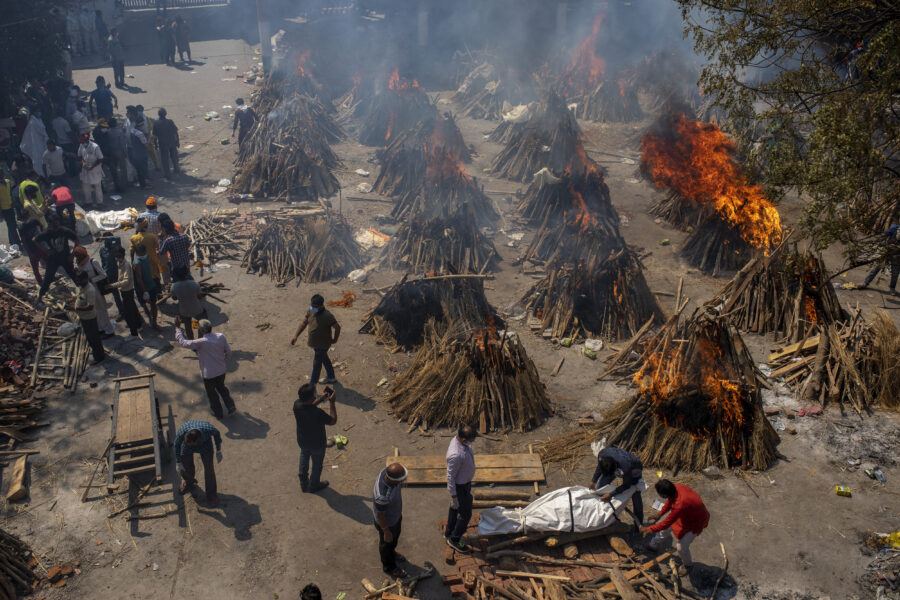 FILE – In this April 24, 2021, file photo, multiple funeral pyres of victims of COVID-19 burn at a ground that has been converted into a crematorium for mass cremation in New Delhi, India. India's death toll from COVID-19 has surpassed 200,000 as a virus surge sweeps the country, rooted in so-called super-spreader events that were allowed to happen in the months following the autumn when  the country had seemingly brought the pandemic under control. (AP Photo/Altaf Qadri, File)