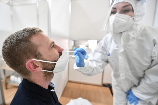An employee in protective clothing takes a swab from a man in the Corona test centre at the trade fair in Erfurt, Germany, Wednesday, April 28, 2021. The rapid test centre is operated primarily for visitors to the Federal Horticultural Show in exhibition hall three of the fair grounds. (Martin Schutt/dpa via AP)