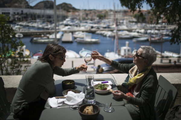 """Charlotte Barrau and her mother Dany Barrau share a toast on a restaurant terrace, in La Ciotat southern France, Wednesday, May 19, 2021. Cafe and restaurant terraces reopened Wednesday after a pandemic shutdown of more than six months deprived people of what feels like the essence of life in France. The French government is lifting restrictions incrementally to stave off a resurgence of COVID-19 and to give citizens back some of their signature """"joie de vivre.""""(AP Photo/Daniel Cole)"""