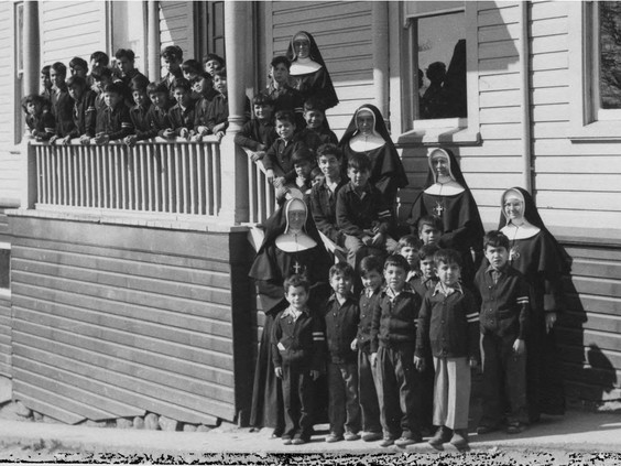 Catholic church officials with Indigenous children outside the St. Paul's Indian Residential School in North Vancouver. PHOTO BY INDIAN RESIDENTIAL SCHOOL HISTORY AND DIALOGUE CENTRE /PNG
