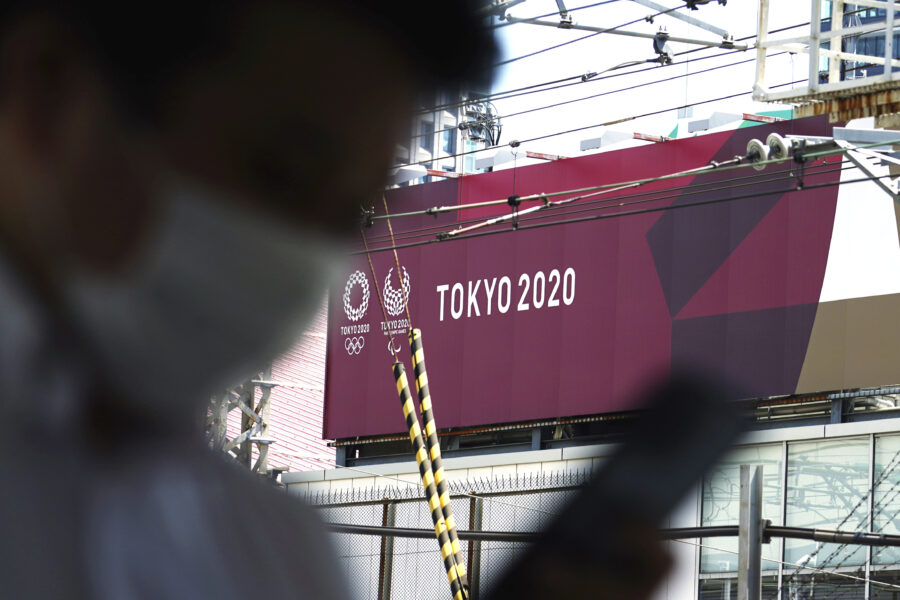 "A man wearing a protective mask to help curb the spread of the coronavirus walks past a banner for the Tokyo 2020 Olympic and Paralympic Games at the start of Japan's ""Golden Week"" holidays Friday, April 30, 2021, in Tokyo. The Japanese capital confirmed more than 690 new coronavirus cases on Friday. (AP Photo/Eugene Hoshiko)"