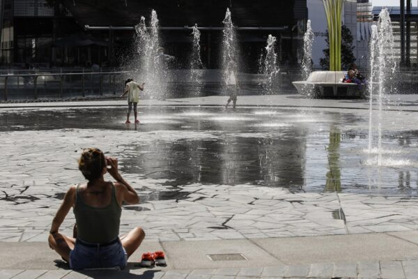 A woman drinks as children cool-off in a public fountain in Milan, Italy, Friday, July 31, 2020. The first heat wave of the summer, which arrived Thursday and will last at least until next Saturday, will reach temperatures over 34 Celsius (104 Fahrenheit). (AP Photo/Luca Bruno)