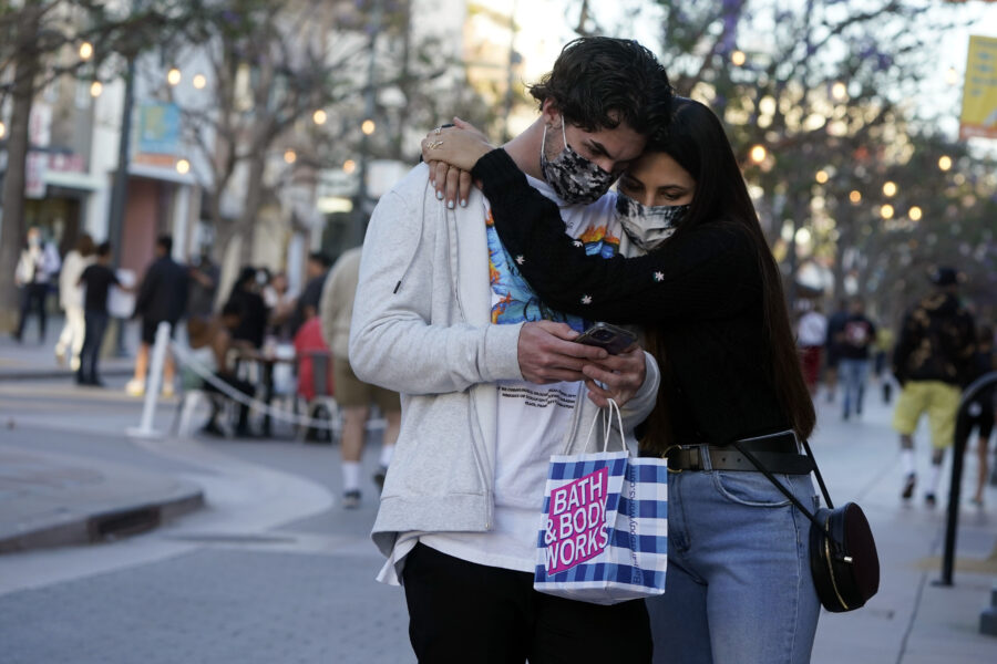 Shoppers embrace and wear masks amid the COVID-19 pandemic on The Promenade Wednesday, June 9, 2021, in Santa Monica, Calif. (AP Photo/Marcio Jose Sanchez)