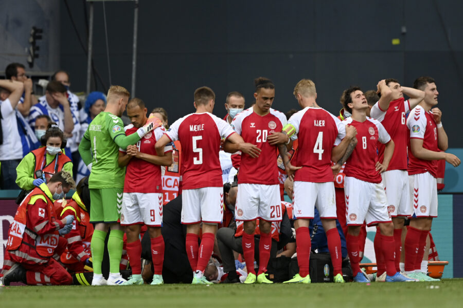Denmark players make a wall around teammate Christian Eriksen being assisted by medics during the Euro 2020 soccer championship group B match between Denmark and Finland at Parken Stadium in Copenhagen, Saturday, June 12, 2021. (Stuart Franklin/Pool via AP)
