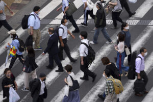 People wearing protective masks to help curb the spread of the coronavirus walk along a pedestrian crossing Wednesday, June 16, 2021, in Tokyo. The Japanese capital confirmed more than 500 new coronavirus cases on Wednesday. (AP Photo/Eugene Hoshiko)