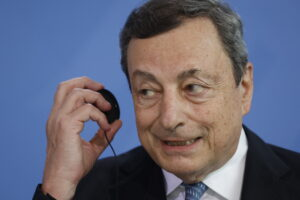 Italy's Prime Minister Mario Draghi takes his head set off after giving a press conference after talks ahead of the Euro summit 2021 at the Chancellery in Berlin, Monday June 21, 2021. (Odd Andersen/Pool Photo via AP)
