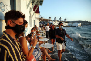 People, some of them wearing face masks against the spread of the new coronavirus, gather in Little Venice on the Aegean Sea island of Mykonos, Greece, Sunday, Aug. 16, 2020. Wary of a rise in daily coronavirus cases that threatens to undo its relative success in containing the pandemic so far, the Greek government is imposing local restrictions on businesses, especially those that cater to big crowds, and business owners on the island of Mykonos don't like it one bit. (AP Photo/Thanassis Stavrakis)