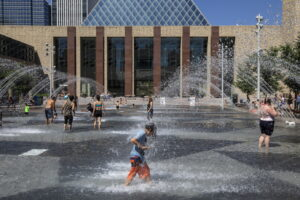 People cool off in the city hall pool, as temperatures hit 37 degrees Celsius in Edmonton, Alberta, on Wednesday, June 30, 2021. (Jason Franson/The Canadian Press via AP)