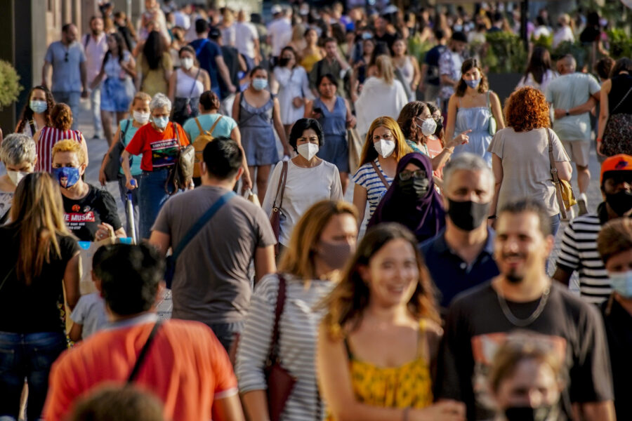 People wearing a face mask to protect against the spread of coronavirus walk along a street in downtown Barcelona, Spain, Saturday, July 3, 2021. The need to speed up vaccine rollouts has become more urgent as the COVID-19 delta variant spreads quickly. (AP Photo/Joan Mateu)