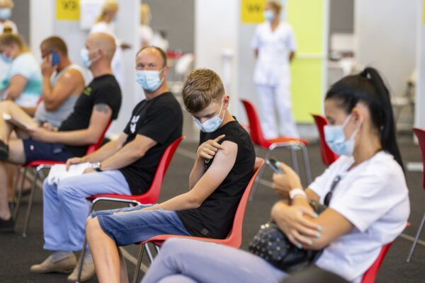 Joonas Leis , 12 years old boy, center, as his father Kuldar, left of him, rest after getting a shot a coronavirus vaccine at a vaccination center inside a sports hall in Estonia's second largest city, Tartu, 164 km. south-east from Tallinn, Estonia, Thursday, July 29, 2021. Estonia's second largest city Tartu is making rapid progress in vaccinating children aged 12-17 ahead of the school year in September. Around half of the town's teenagers have already received their first vaccine, and local health officials are confident they will hit 70% in the coming 30 days. (AP Photo/Raul Mee)