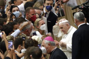 Pope Francis exchanges his skull cap with another one he was given by faithful at the end of his weekly general audience in the Paul VI hall at the Vatican, Wednesday, Aug. 4, 2021. Pope Francis on Wednesday resumed his routine of weekly audiences with the general public a month after he underwent bowel surgery, expressing his desire to visit someday Lebanon, as he recalled the first anniversary of the devastating Beirut port explosion. (AP Photo/Riccardo De Luca)
