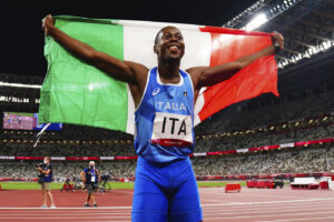 Eseosa Desalu of Italy celebrates after winning gold in the final of the men's 4 x 100-meter relay at the 2020 Summer Olympics, Friday, Aug. 6, 2021, in Tokyo, Japan. (Aleksandra Szmigiel/Pool Photo via AP)