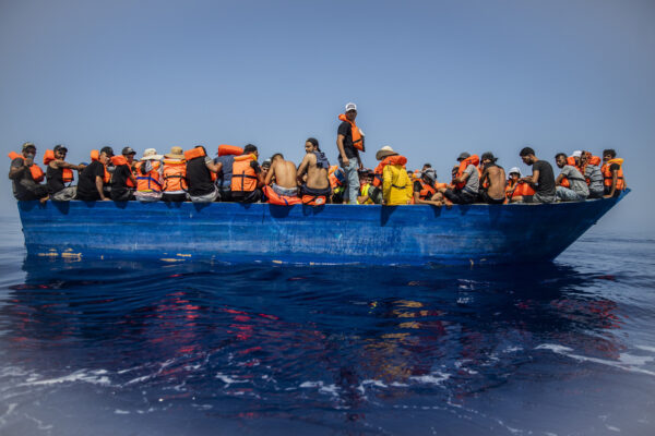 A group thought to be migrants from Tunisia aboard a precarious wooden boat waiting to be assisted by a team of the Spanish NGO Open Arms, around 20 miles southwest from the Italian island of Lampedusa, in Italian SAR zone, Thursday July 29, 2021.  The NGO assisted more than 170 people who arrived next to the Italian island on board six different wooden dinghies, before the Italian authorities took them to land. (AP Photo/Santi Palacios)