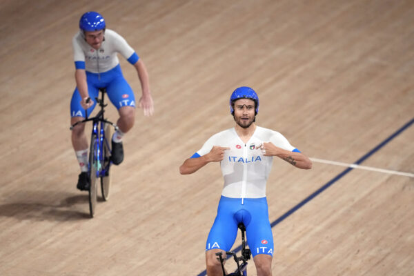 Filippo Ganna, right, and Simone Consonni of Team Italy celebrate after winning their heat during the track cycling men's team pursuit at the 2020 Summer Olympics, Tuesday, Aug. 3, 2021, in Izu, Japan. (AP Photo/Christophe Ena)