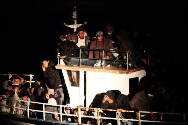 Lapresse 07-03-2011 Lampedusa, Italia Cronaca Nella notte un migliaio di clandestini sbarcano a Lampedusa, 10 barconi raggiungono l' Isola. Nella foto la motovedetta della guardia di finanza illumina un barcone carico di migranti    Lapresse 07-03-2011 Lampedusa Island, Italy Resumed at full speed landings of illegal tunisians immigrants on the lampedusa island