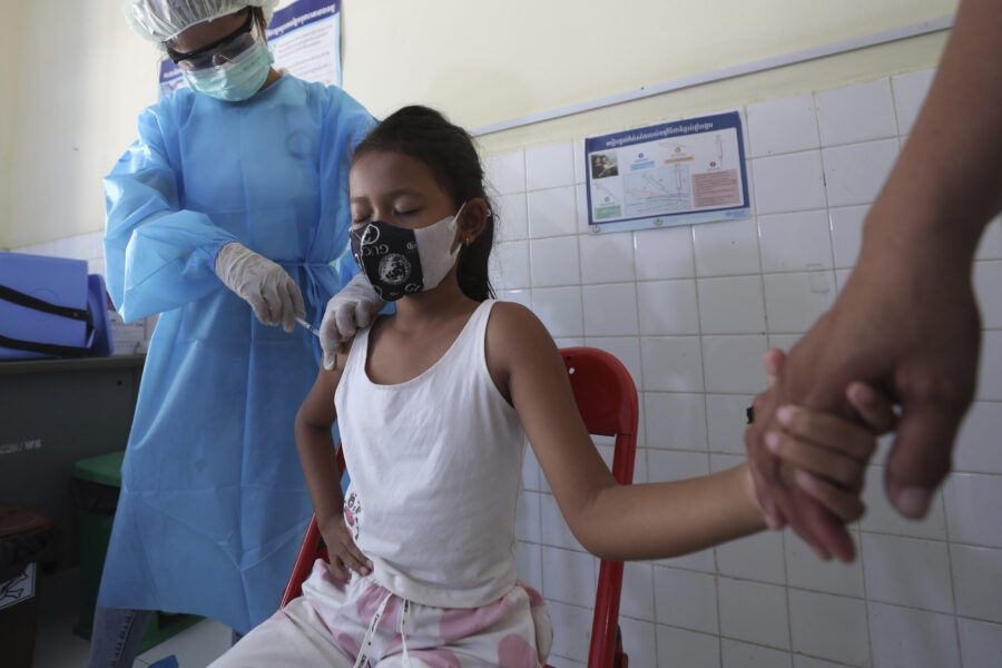 A young girl holds her mother's hand as she receives a shot of the Sinovac's COVID-19 vaccine at a Samrong Krom health center outside Phnom Penh, Cambodia, Friday, Sept. 17, 2021. Prime Minister Hun Sen announced the start of a nationwide campaign to give COVID-19 vaccinations to children between the ages of 6 and 11 so they can return to school safely after a long absence due to measures taken against the spread of the coronavirus. (AP Photo/Heng Sinith)